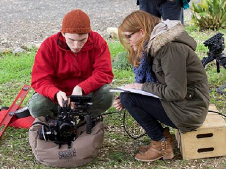 Two students setting up a camera on grassy ground.
