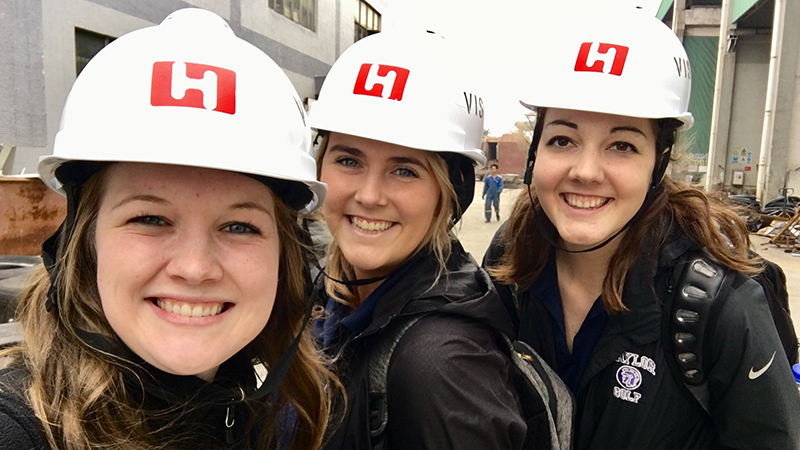 Three females students in hard hats.