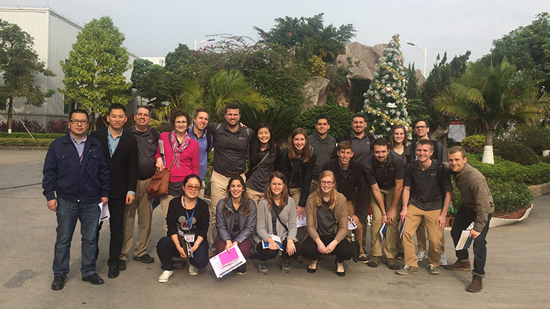 Group of students with their Chinese hosts standing in front of a garden.