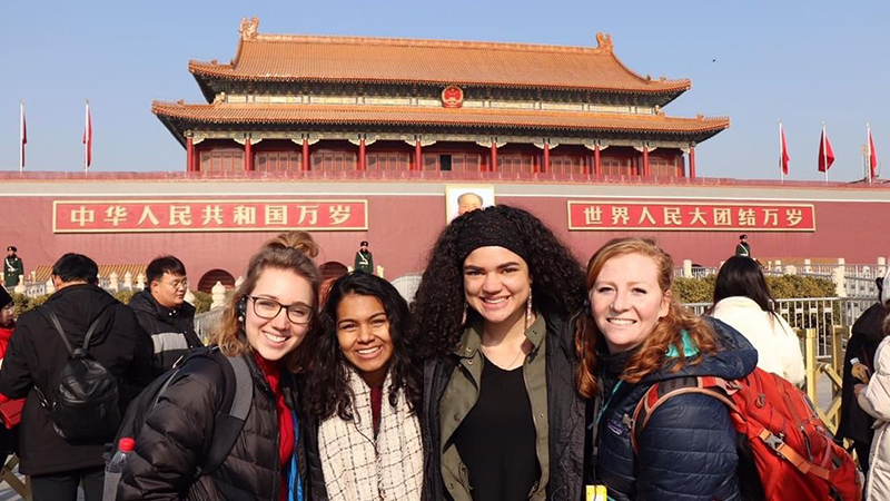 4 female students standing in front of the fordidden city in China.