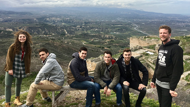 Six students posing on ancient ruins over looking rocky hills.