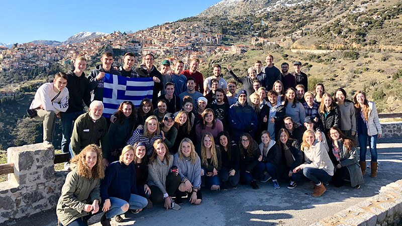 A group of students and faculty standing in front of a historic city while holding the Greece flag during a J-term trip.