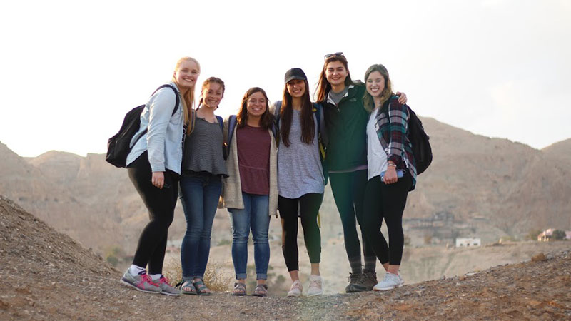 six female students standing on a rocky desert hill overlooking a town.