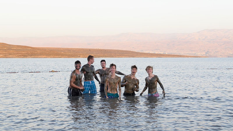 six male students covered in mud and standing waist deep in water.