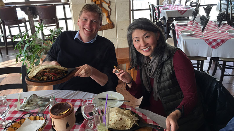 Professor May Young and Professor Hank Voss showing off the traditional food they ordered at a resteraunt.