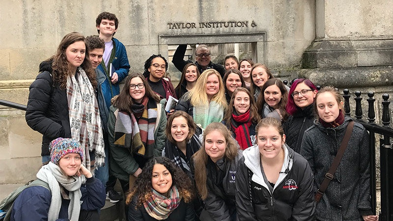 A  group of students standing outside the Taylor Institution, a library at Oxford University.