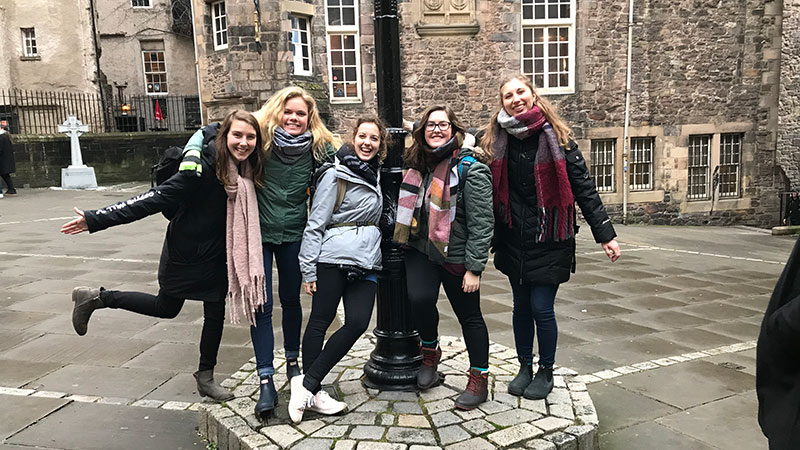 Five girls standing around a lamp post in a stone brick courtyard.